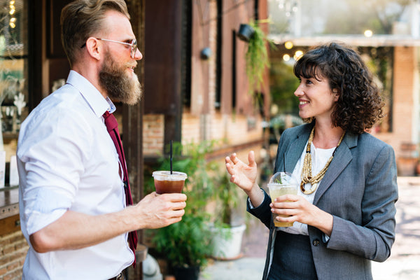 a man and woman drinking cold-brew outside