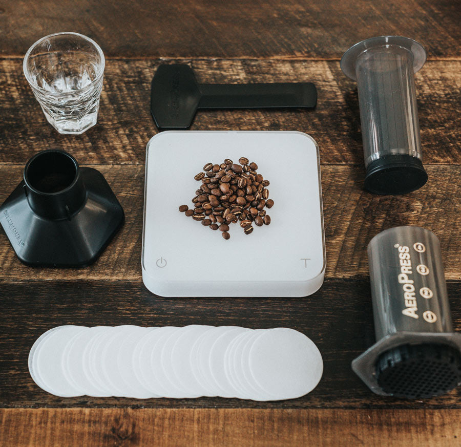 An AeroPress and all of its components laid out flat on a table along with a scale and coffee beans