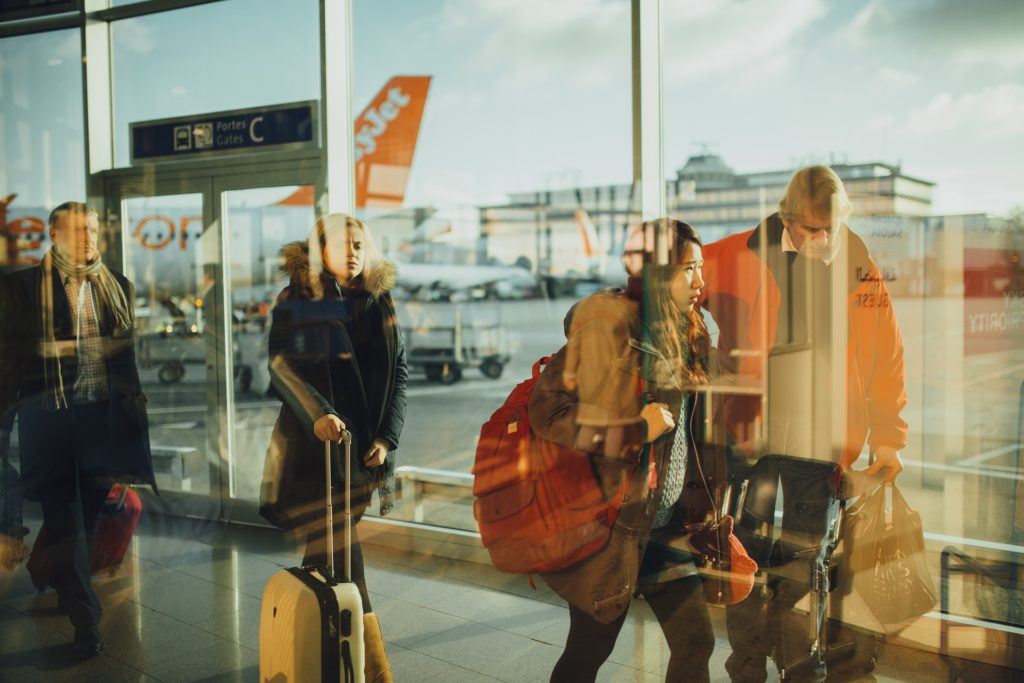 Travelers are reflected in the windows of an airport with an airliner jet being loaded outside
