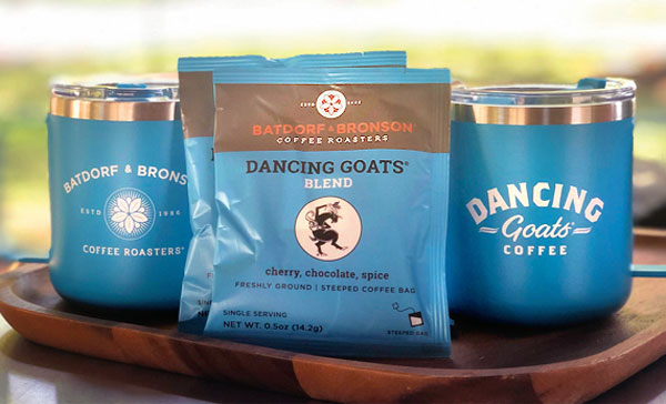 Two Dancing Goats<sup>®</sup> Steeped coffee packets sit on a wooden tray beside two Batdorf and Bronson Camper Mugs