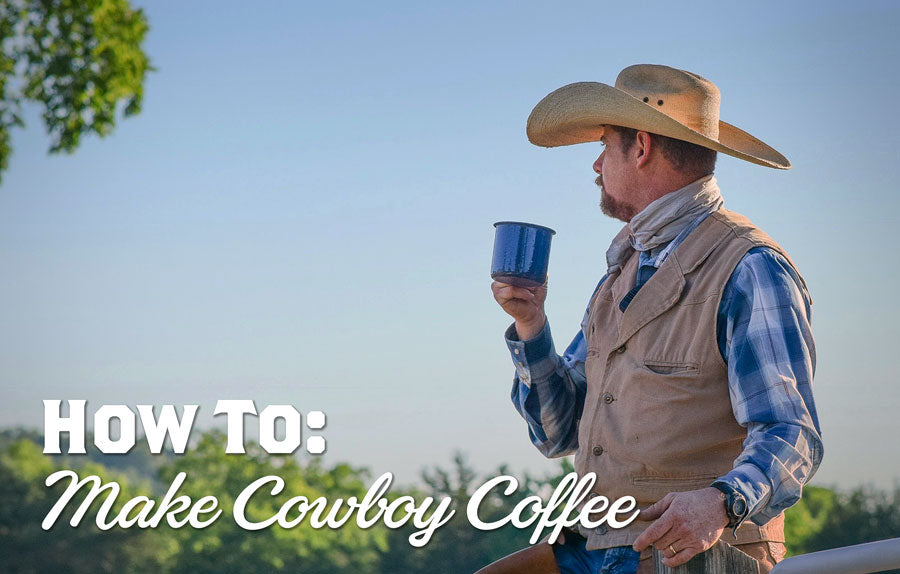 A Cowboy sits on a fence while holding a mug of coffee and looking off into the distance