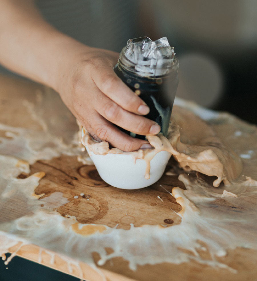 A hand places a glass of iced coffee into a mug containing a latte, coffee splashes everywhere