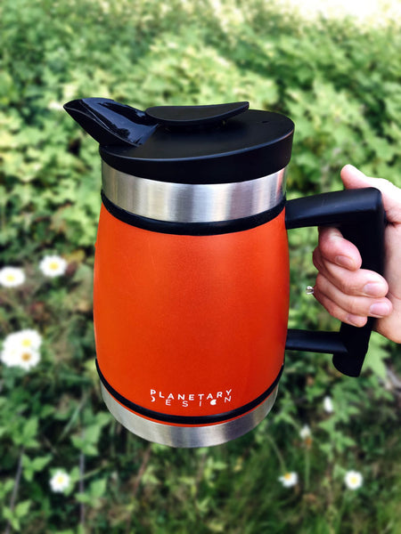 A hand holds the Planetary Design French Press in the air above a field of daisies.
