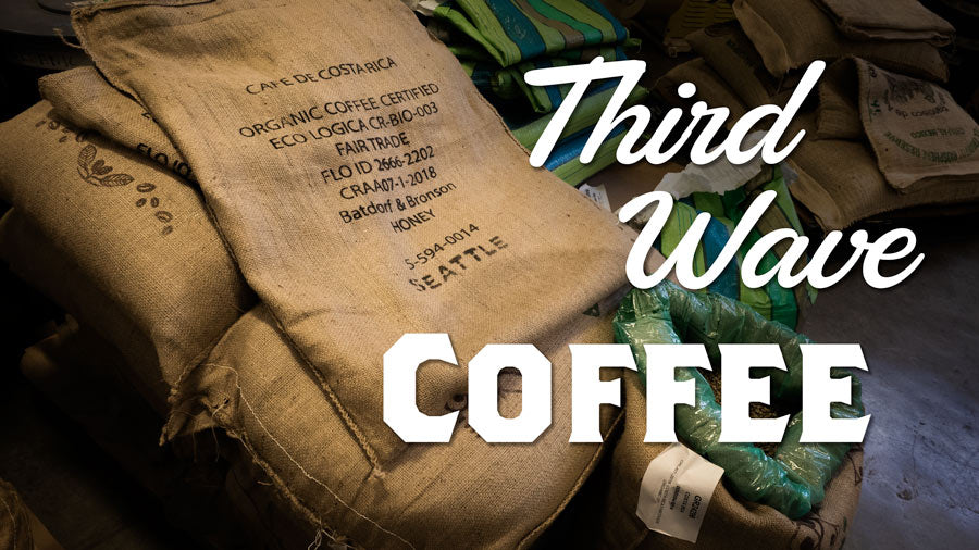 Burlap bags of green coffee beans stacked in a warehouse with the words Third Wave Coffee overlain