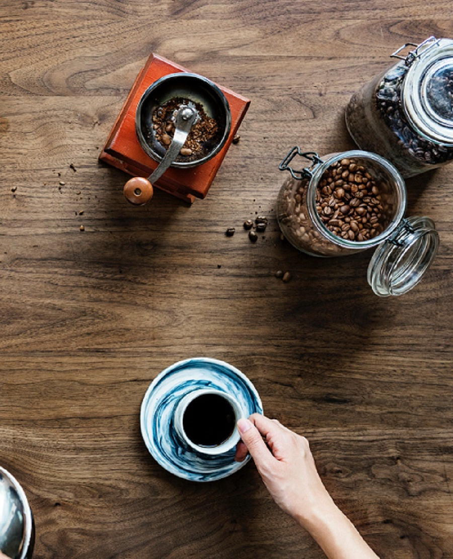 Looking down at a table with coffee beans, a hand coffee grinder, and a cup of coffee.