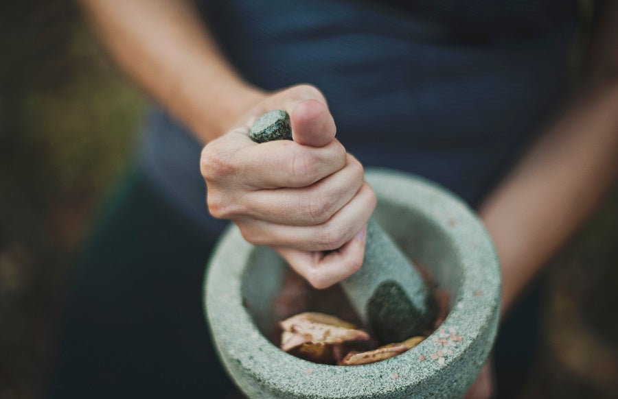 Hands using a mortar and pestle to pulverize coffee
