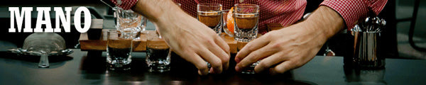 a short wide image of two hands carefully arranging a row of coffee-filled shot glasses on a countertop with the word Mano appearing in the center