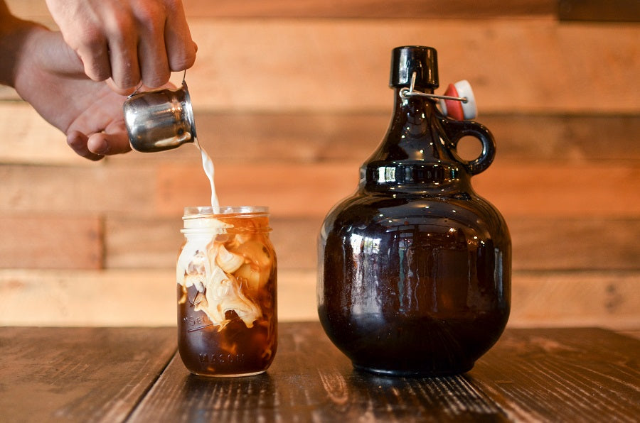 Growler of Toddy next to a cup of toddy with milk