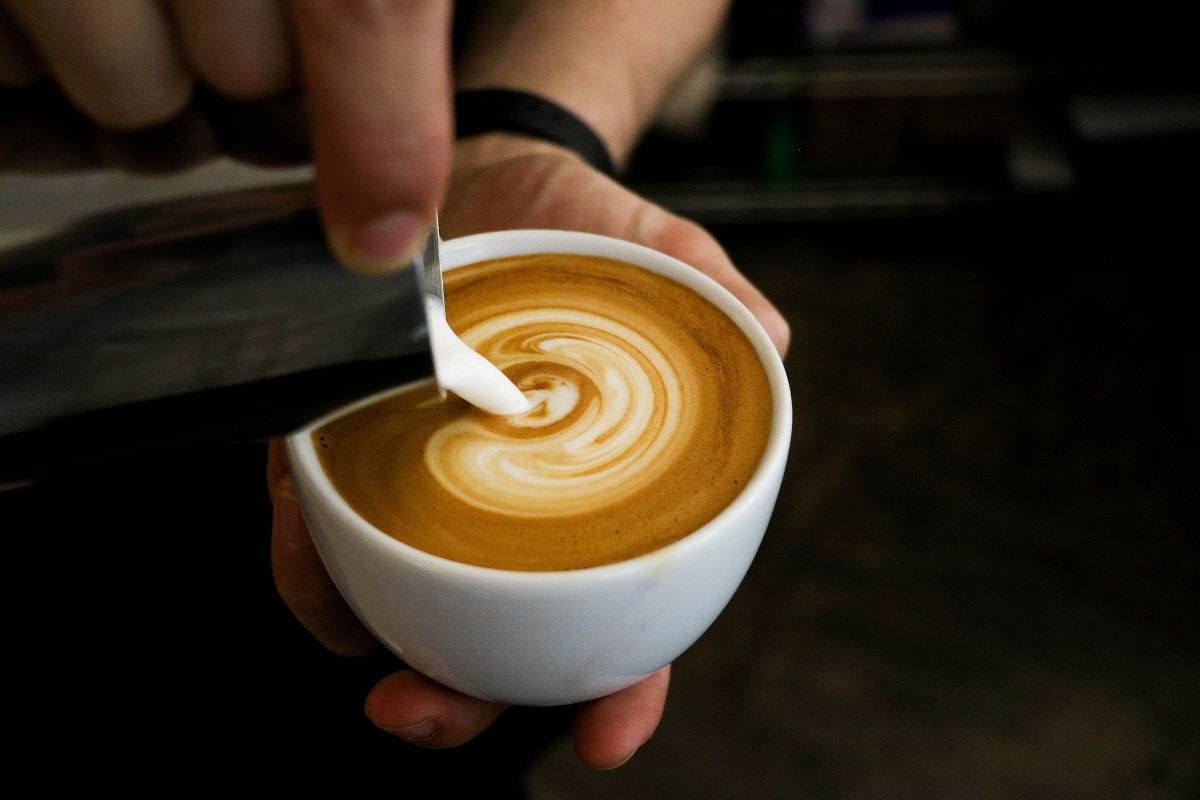 pouring milk into a cup with espresso