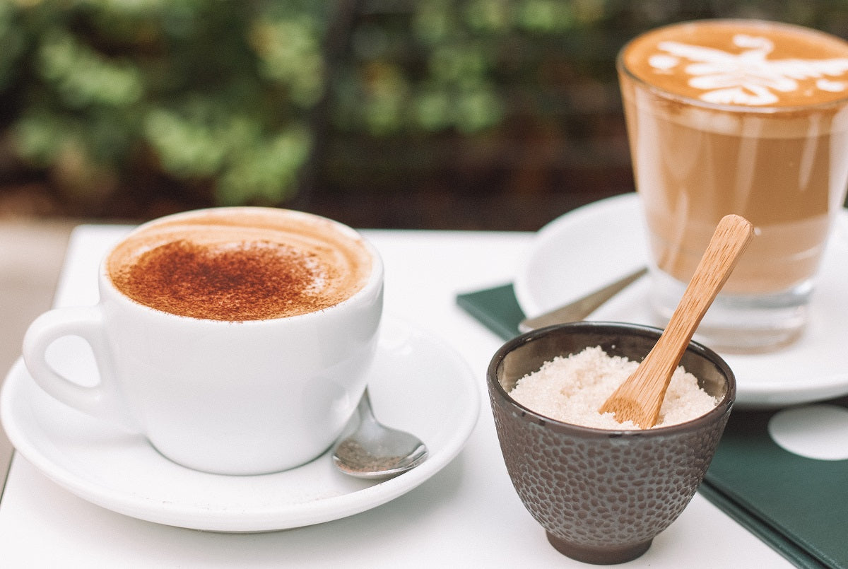 a latte with cinnamon powder on it and a bowl of sugar next to it