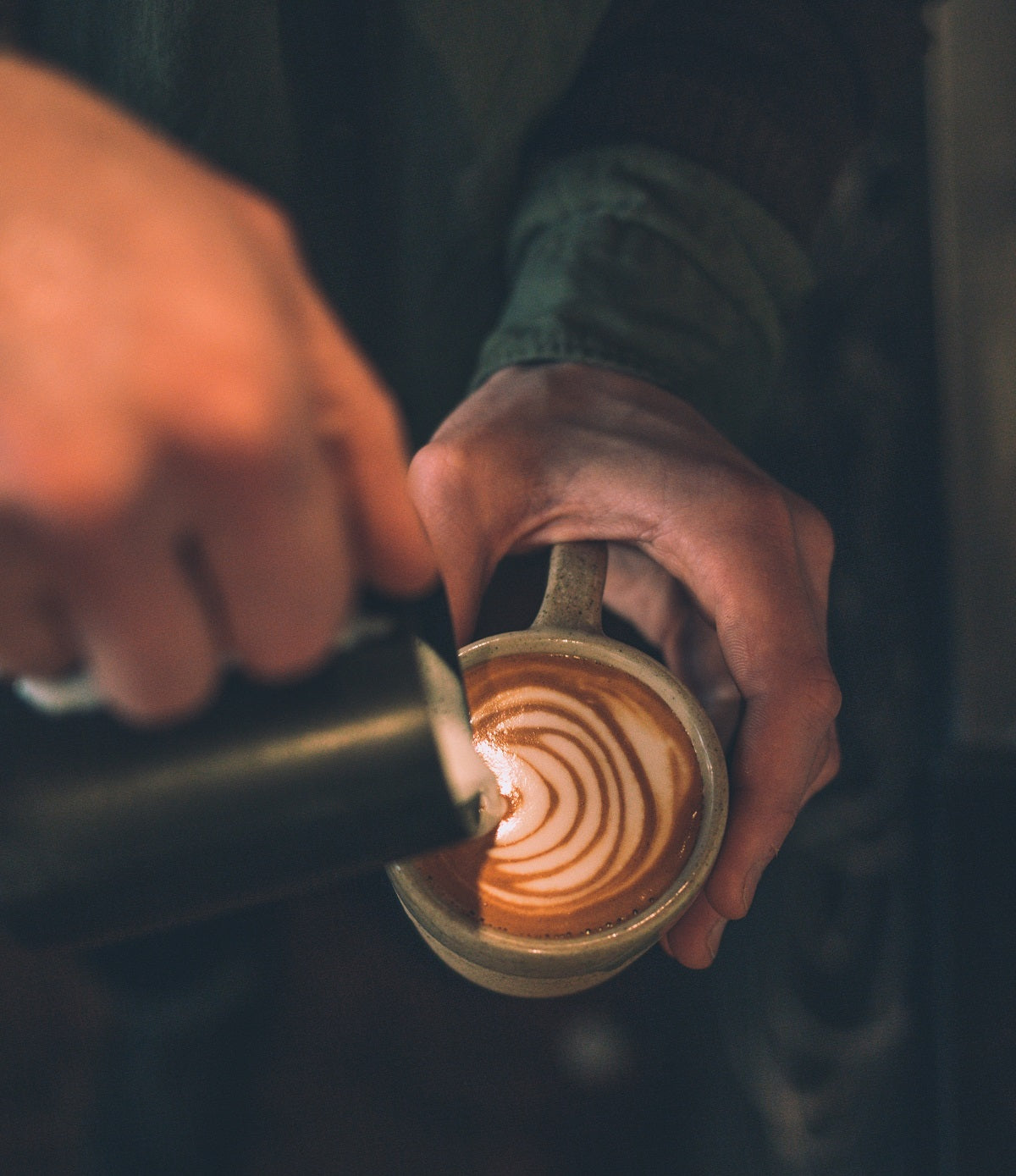 pouring steamed milk into cup with espresso
