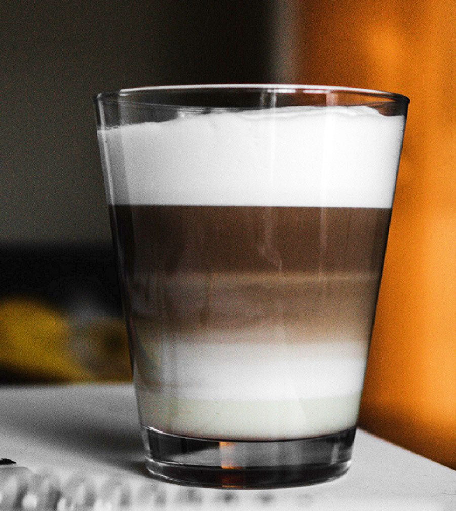 A clear glass illustrated the 3-part ratio of a traditional cappuccino