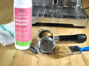 a bottle of coffee machine cleaning powder sits on a countertop alongside a flat-head screw driver and a paint-brush and assorted espresso machine parts