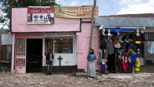 a street view of two shop fronts in Ethiopia, one is painted pink, the other blue, a woman stands out front wearing a blue top and grey skirt