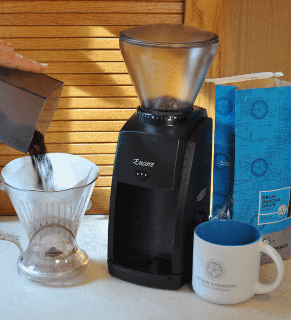 How to Choose a Coffee Grinder - A photo depicting a coffee grinder, mug, and ground coffee in a kitchen.