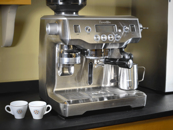 a fully equipped Breville espresso machine sits on a counter beside portafilter and ristretto cups