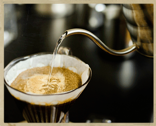 A gooseneck kettle pours hot water over coffee grounds in a clever dripper coffee maker.