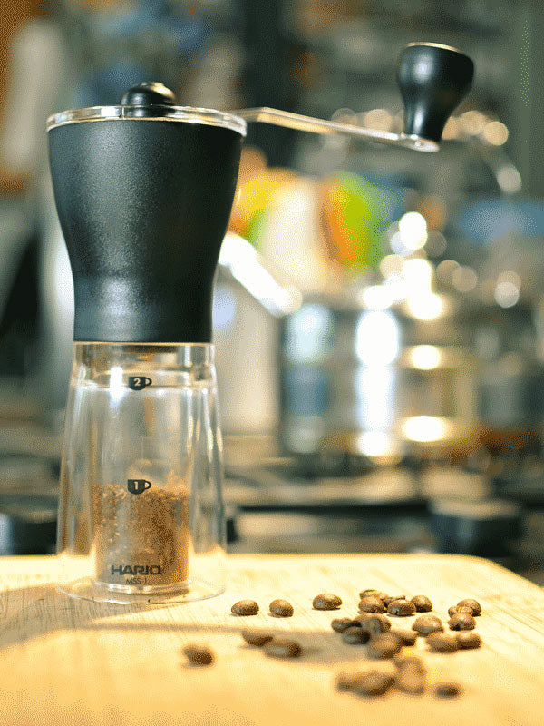 How to Choose a Coffee Grinder - A photograph depicting a Hario Mini Mill manual grinder standing on a kitchen counter top