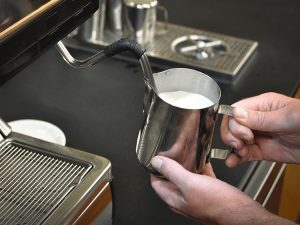milk is steamed in a stainless steel pitcher using the steam-wand attached to the side of an espresso machine