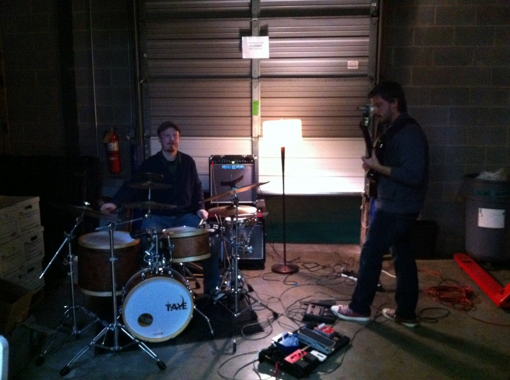 a guitarist and drummer play music on an impromptu stage in the corner of a warehouse