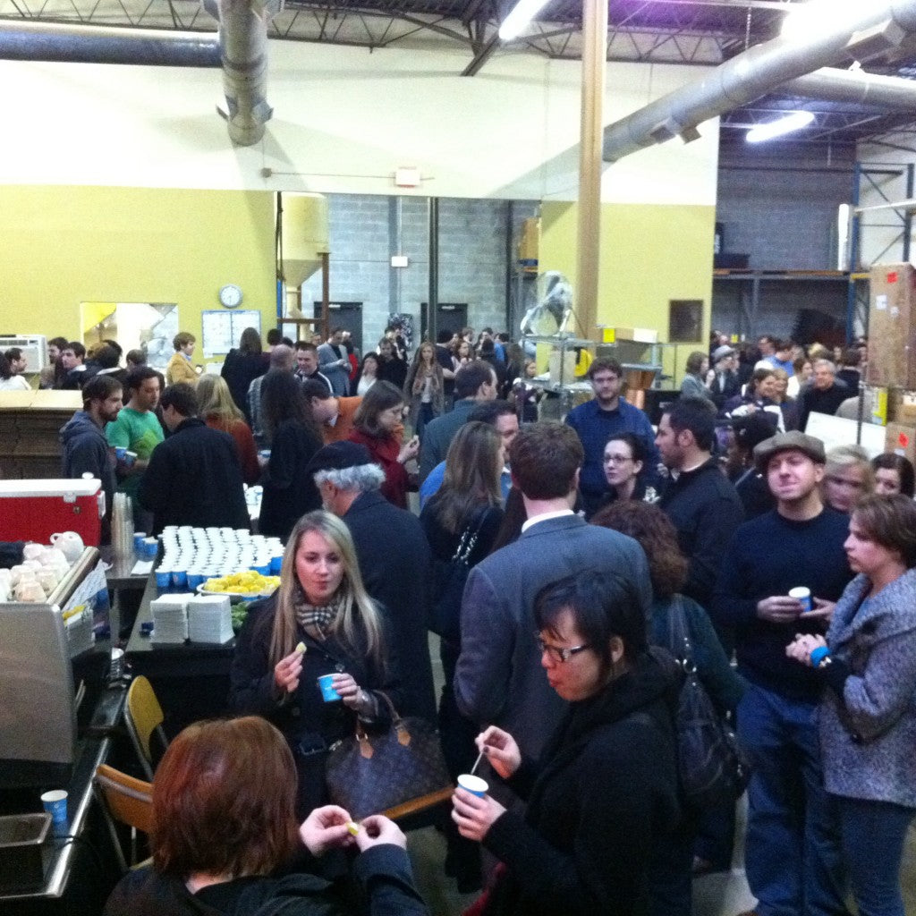 a crowd of people inside a warehouse all holding little blue sample cups