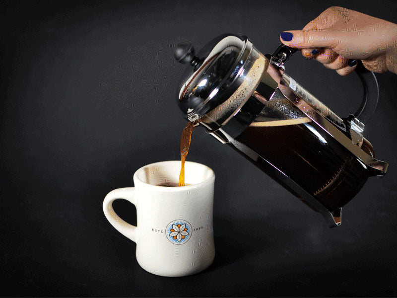 How to use a French Press - A photo of coffee being poured out of a French Press into a coffee mug.