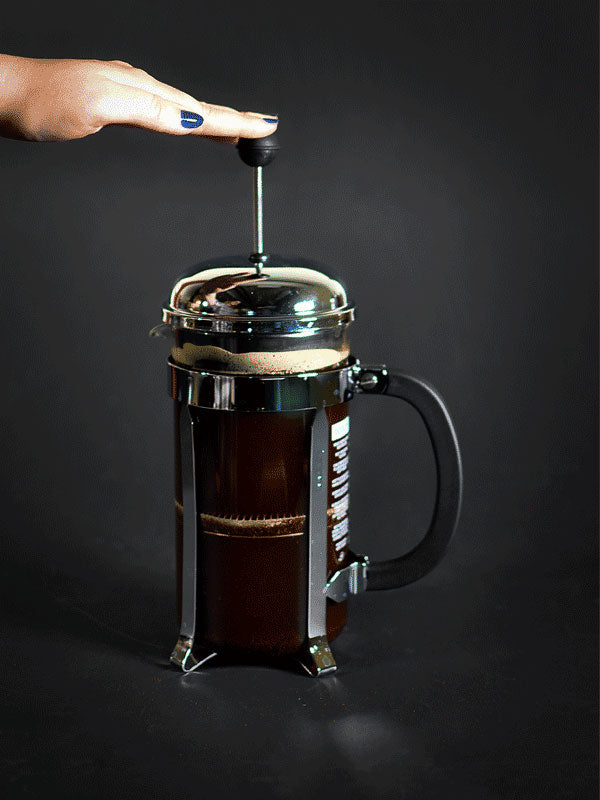 How to use a French Press - A photograph of a hand pressing the plunger of a French Press.