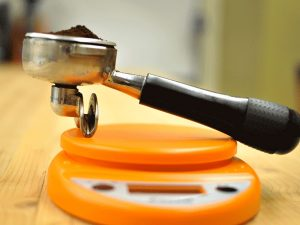 a portafilter loaded with coffee sits on a kitchen scale