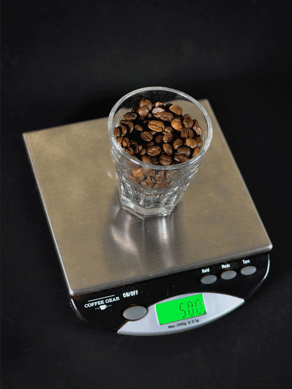 How to use a French Press - A photograph showing a shot glass filled with coffee beans being weighed on a digital kitchen scale