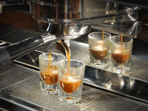 two shot glasses collect the espresso that drips from the portafilter on an espresso machine