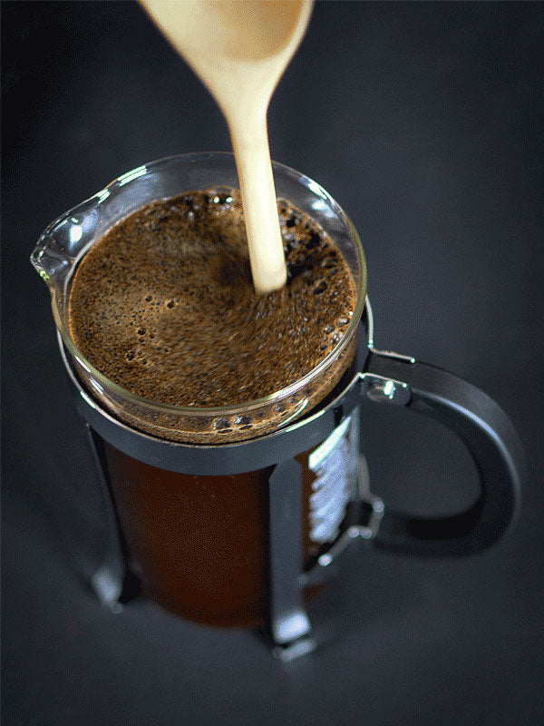 How to use a French Press - A photo of a wooden spoon being used to stir the coffee in a French Press.
