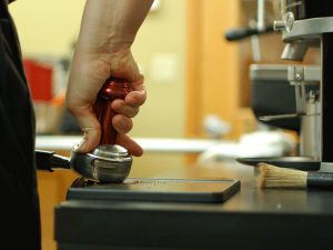 low-angle side view of a tamper being used to compress the coffee in a portafilter