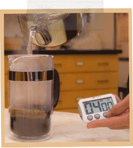 A hand holds a timer which reads 4 minutes, while hot water is poured over coffee grounds in a French Press