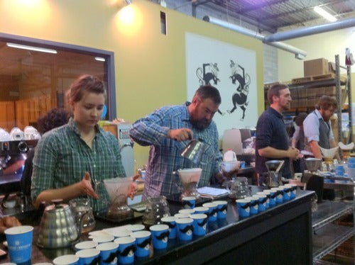 four Batdorf employees brewing pourover coffee behind the bar