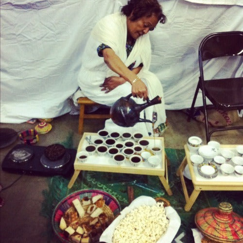 a woman sits behind a table pouring coffee for a traditional Ethiopian coffee ceremny