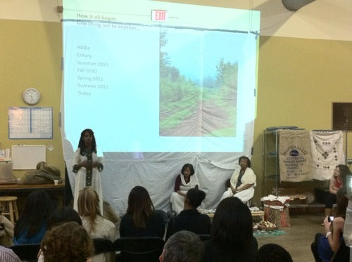 three women demonstrate traditional Ethiopian coffee ceremony in front of an audience of coffee enthusiasts