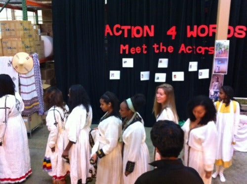 Performers line up on stage following a performance, Action 4 Words is printed on the backdrop