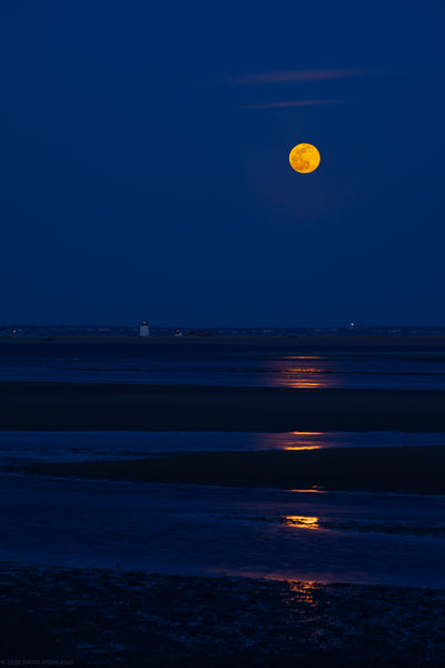 The March full moon rises over Long Point lighthouse in Provincetown, MA.