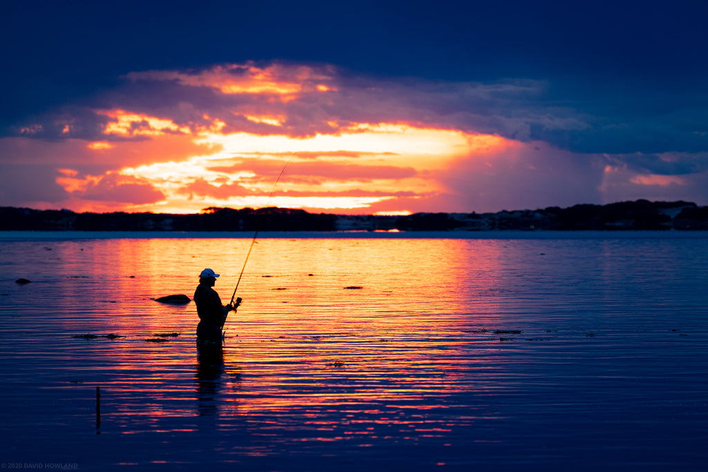 A fisherman at sunset over Cape Cod Bay