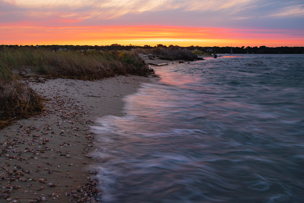 Sunset at high tide on a beach full of seashells on Cape Cod
