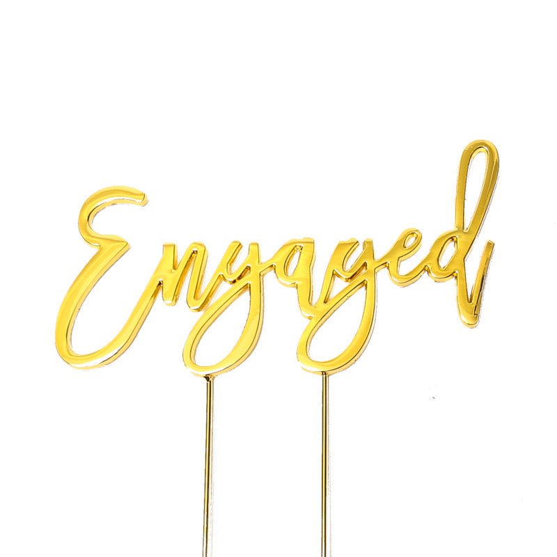 Metal cake topper with the word Engaged in Gold