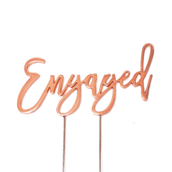 Metal cake topper with the word Engaged in Rose Gold