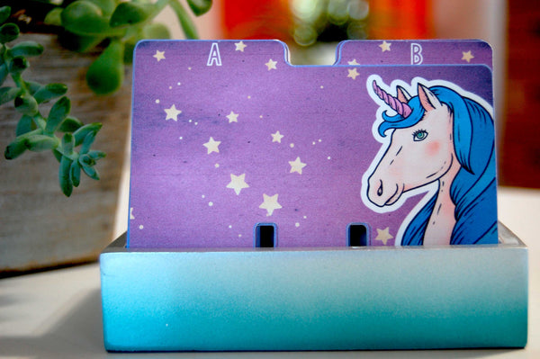 A set of colorful Rolodex dividers in a teal holder with plants in the background. The Rolodex dividers are a celestial purple sky with a unicorn bust in the corner.