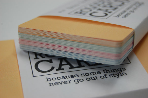 A bundle of 28 wrapped Mini Rolodex Refill Cards shown along the edge. The orange are on top followed by green, pink and blue.