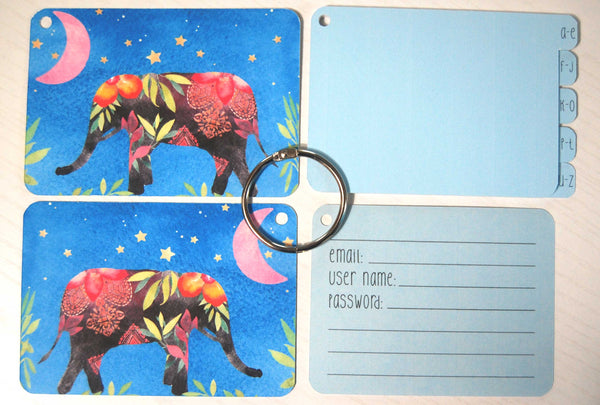 Flat lay display of all of the elements of the elephant password keeper: Front and back cover, silver ring, 5 blue dividers, and 40 blue password cards