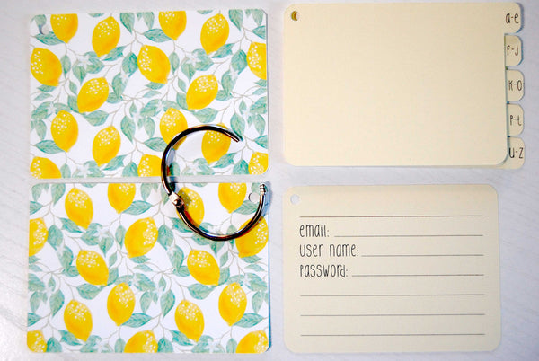 Flat lay display of all of the elements of the lemon password keeper: Front and back cover,  silver ring, 5 yellow dividers, and 40 yellow password cards