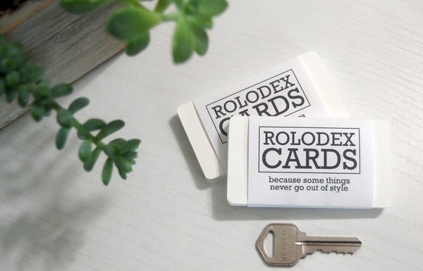 Two wrapped bundles of mini Rolodex cards with a key for size comparison