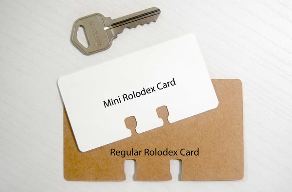 A tiny Rolodex card (white) with a key and a regular Rolodex card (kraft paper brown) for size reference