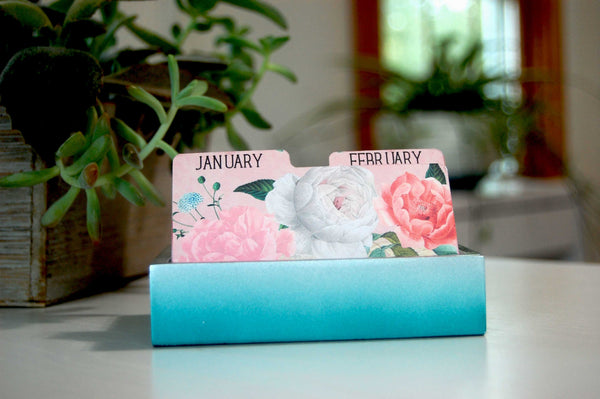 Pretty Floral Monthly Rolodex Dividers in a vintage shabby rose print. They are in a Rolodex holder with plants in the background.