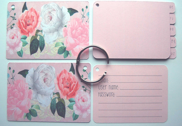 Flat lay display of all of the elements of the pink shabby rose password keeper: Front and back cover, silver ring, 5 pink dividers, and 40 pink password cards